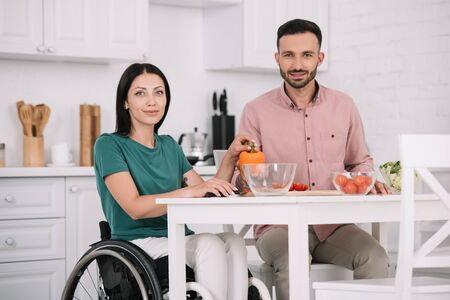 attractive disabled woman with boyfriend smiling at camera while sitting at kitchen table and preparing salad together