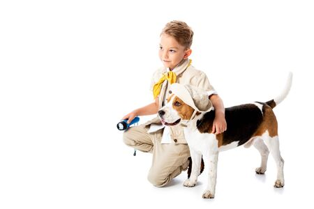 smiling explorer child embracing cute beagle dog in hat and holding flashlight on white