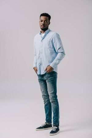 handsome african american man standing with hands in pockets on grey