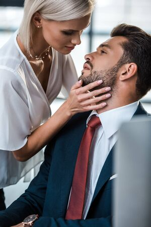 selective focus of passionate blonde woman touching face of handsome man in office