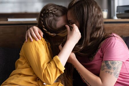two lesbians covering faces with hair while embracing and kissing in living room