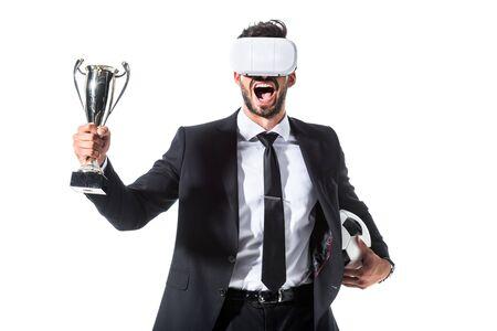 Uomo d'affari eccitato in cuffia per realtà virtuale con pallone da calcio e coppa del trofeo isolato su bianco Archivio Fotografico