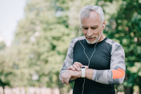 handsome mature sportsman looking at fitness tracked while listening music in earphones