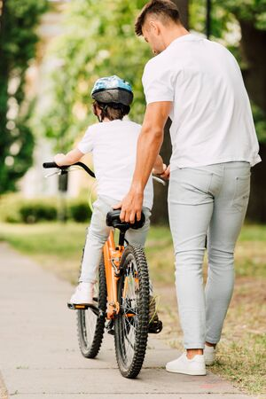 full length view of father helping son to ride on bicycle by holding sit of bike