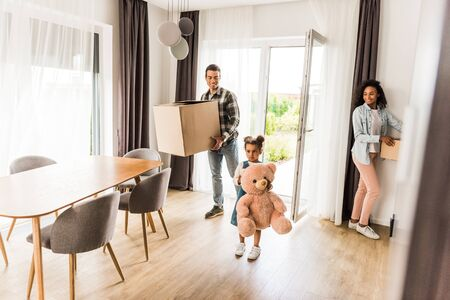 full length view of african american family walking into house while parents holding boxes and kid holding teddy bear Stockfoto