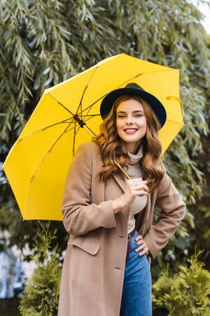 attractive woman in blue hat looking at camera and holding yellow umbrella