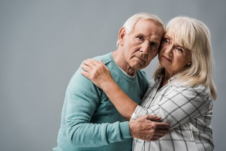 senior woman with grey hair hugging upset husband on grey