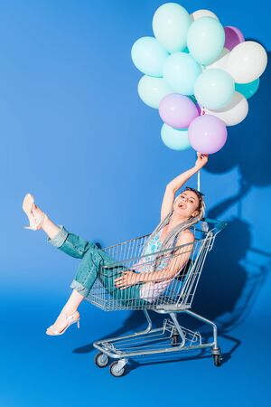 beautiful stylish girl in shopping cart with balloons smiling on blue