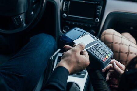 vista ritagliata del cliente che paga con carta di credito vicino all'auto