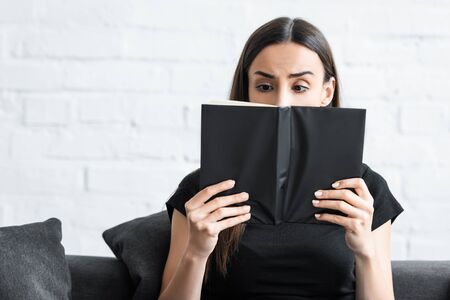 disappointed young woman covering face with notebook while suffering from dementia at home
