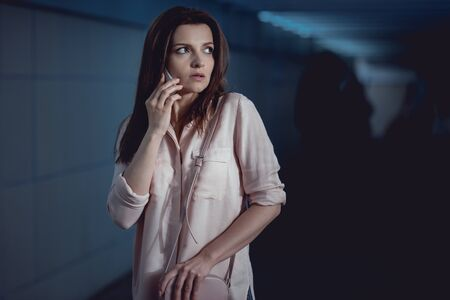 frightened beautiful woman talking on smartphone in underpass Stock Photo