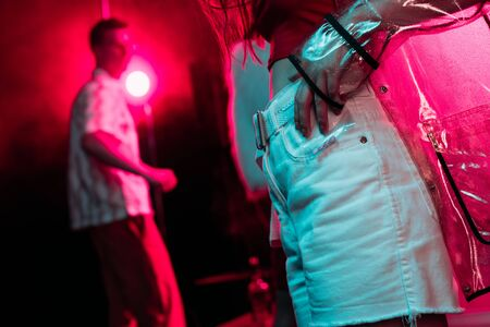 cropped view of girl holding plastic zipper bag with drugs in nightclub