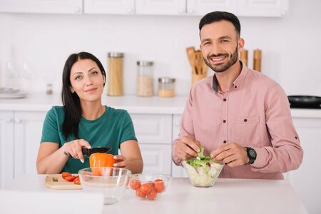 happy couple looking at camera while sitting at kitchen table and preparing salad together
