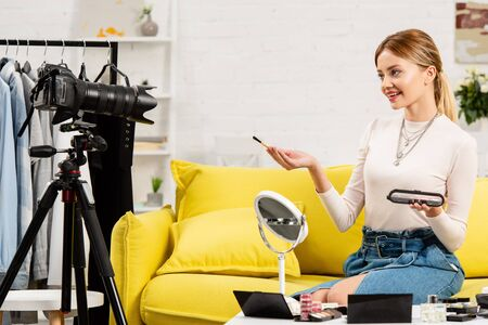 beauty blogger doing makeup in front of video camera at home