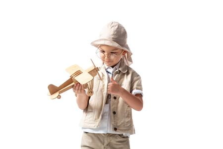 dreamy explorer boy in glasses and hat holding wooden toy plane isolated on white Banco de Imagens - 130117755