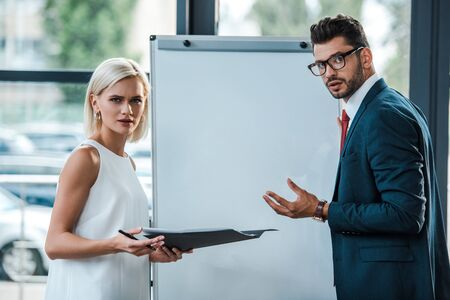 attractive blonde woman holding folder near businessman in glasses gesturing in office