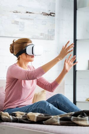 young adult woman playing with virtual reality headset in apartment
