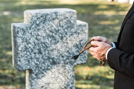 cropped view of man holding rosary beads near tombstone
