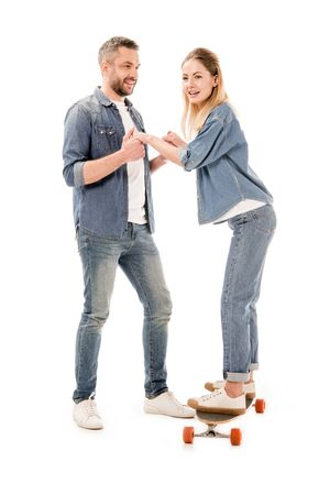 full length view of couple with skateboard holding hands isolated on white Фото со стока