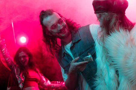 happy man giving weed in plastic zipper bag to girl in nightclub Banco de Imagens