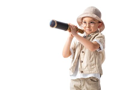 curious smiling explorer boy in glasses and hat holding spyglass isolated on white