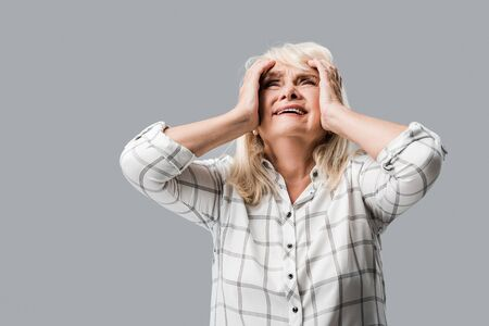 upset retired woman with grey hair touching head isolated on grey
