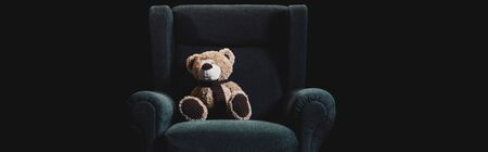 panoramic shot of teddy bear in grey armchair isolated on black