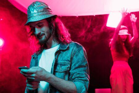 man using smartphone during rave party in nightclub 版權商用圖片