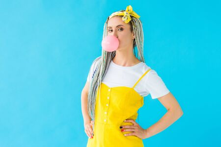 girl with dreadlocks and hands on hips blowing bubblegum isolated on turquoise