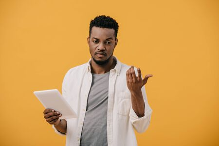 upset african american man gesturing while holding digital tablet isolated on orange