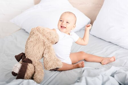 Funny little child in white clothes sitting on bed and laughing while holding plush bear