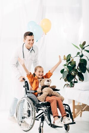 smiling pediatrist and kid with teddy bear on wheelchair in hospital
