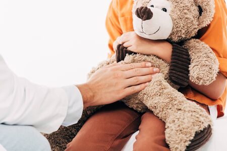 partial view of pediatrist in white coat and kid with teddy bear isolated on white Imagens
