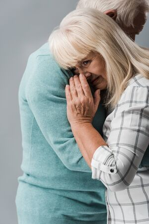 cropped view of husband hugging retired wife covering face while crying isolated on grey