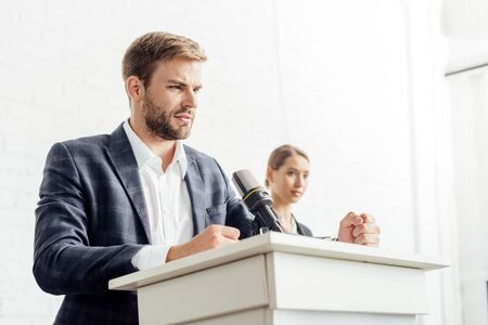 businessman in formal wear talking during conference in conference hall