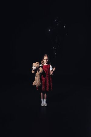 offended kid holding black balloons and teddy bear while looking at camera isolated on black Imagens