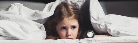 scared child hiding under blanket with flashlight isolated on black