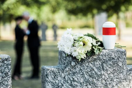 selective focus of bouquet of white flowers and cemetery urn on tombstone