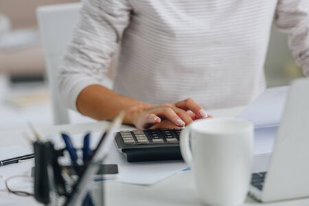 cropped view of woman in white jersey using calculator in apartment
