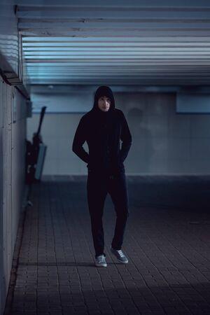 voleur en sweat à capuche noir marchant dans le passage souterrain Banque d'images