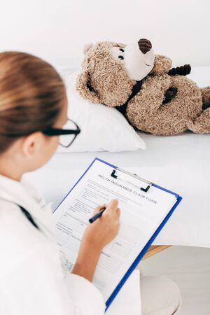 selective focus of child in doctor costume examining teddy bear and writing in clipboard