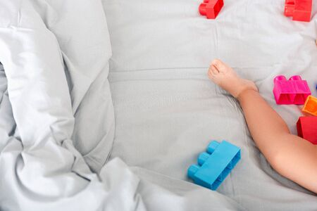 Partial view of barefoot baby leg on bed near colorful construction