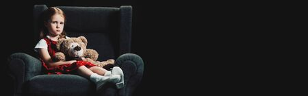 sad, lonely kid sitting in armchair with teddy bear and looking at camera isolated on black Imagens