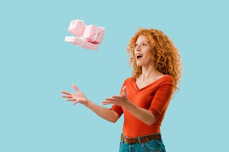 excited redhead girl throwing up gifts isolated on blue