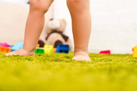 Cropped view of barefoot child standing on green floor among colorful toys
