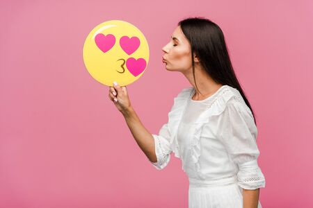 side view of woman holding kissing smiley isolated on pink Stock Photo