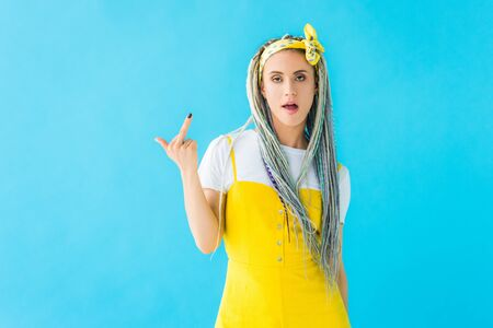 dissatisfied girl with dreadlocks showing middle finger isolated on turquoise Reklamní fotografie