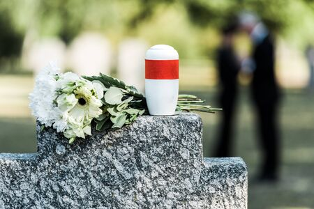 selective focus of flowers and mortuary urn on tomb