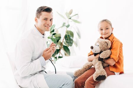 smiling pediatrist in white coat and kid with teddy bear in clinic Imagens