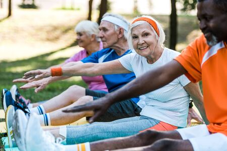 selective focus of multicultural retired women and men in sportswear exercising on fitness mats